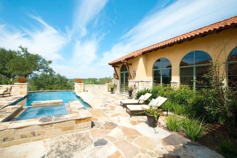 stone paved sidewalk with infiniti pool and hot tub